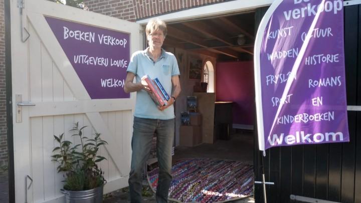 Uitgever Eddy van der Noord voor zijn uitgeverij, waarvan een deel voor de verkoop is ingericht.