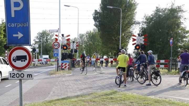 Wandelaars, fietsers en auto's wachten voor de spoorbomen. (Foto: De Vries Media)