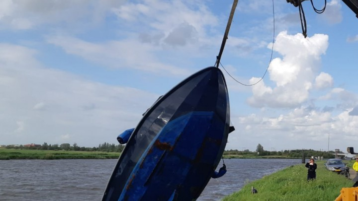 De gezonken vlet wordt geborgen onder toezicht van Provinciale Waterstaat.
