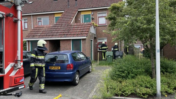 Brandweermannen openen een raam van de benedenwoning. (Foto: Wander Mollema)