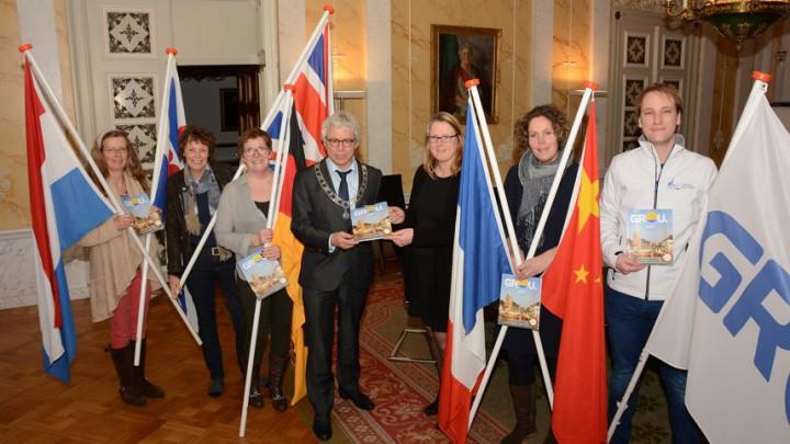Crone krijgt het eerste exemplaar uit handen van Anke Zijlstra, één van de medewerksters van het magazine. Zij en Crone worden geflankeerd door de rest van de medewerkers. De vlaggen geven het internationale karakter van het magazine weer.