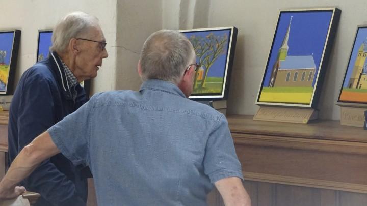 Douwe Bonnema (links) bekijkt met predikant Helmer le Cointre zijn schilderijen van kerken.