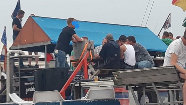 De buurtagent legt opvarenden van een feestboot op de Pikmar de regels uit.