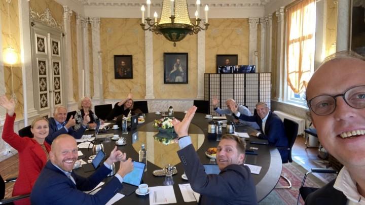Friso Douwstra (rechts) wordt uitgezwaaid door collega's tijdens zijn laatste collegevergadering.