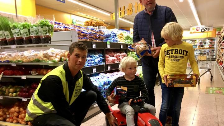 Lenn Cats op de Greydanustrekker met Jumbomedewerker (links), boer Jaap Wilman (achter) en broer (rechts).