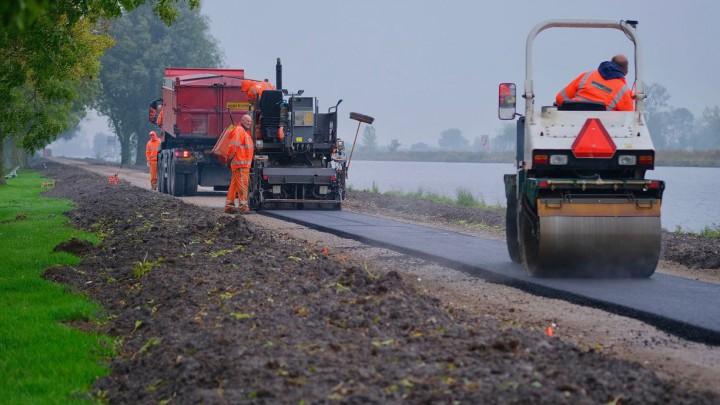 Medewerkers van Oosterhof Holman zijn druk bezig met het asfalteren van het pad. (Foto: Jannes Postma)