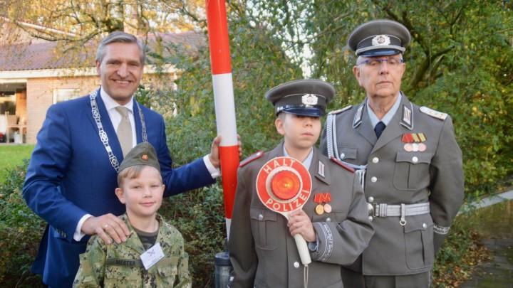 Buma poseert met een jonge soldaat en leden van de Deutsche Volkspolizei (Vopo's) bij de slagboom.