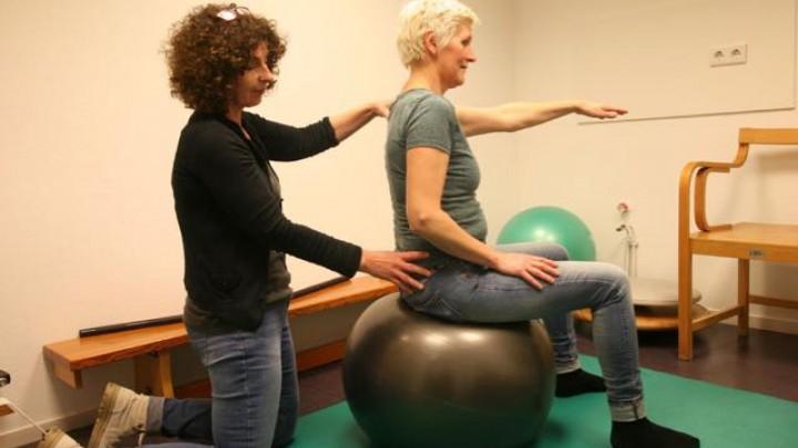 Fysiotherapeut Marion Timmerman aan het werk in haar praktijk. Voor het maken van de foto behandelt ze 'praktijkcollega' Hilda Dijkema.