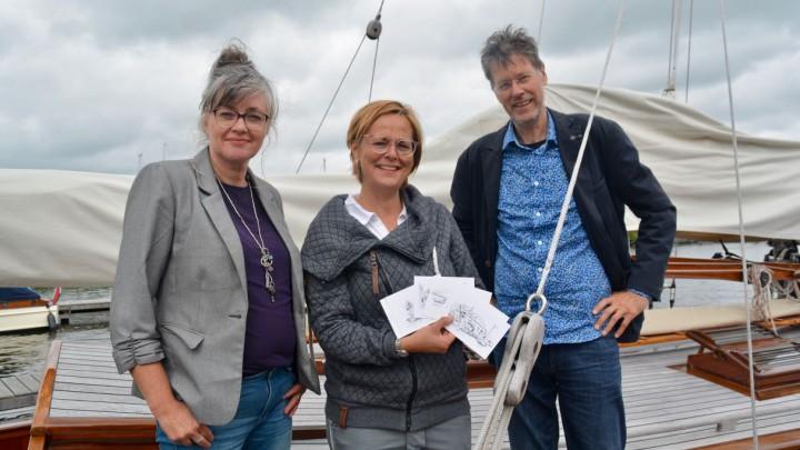 Annemarie Oost (midden) ontving het eerste setje kaarten van ondernemers Eddy van der Noord en Henriët van der Horst.