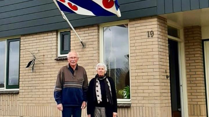 Wim en Marijke poseren voor hun woning aan It Roer, waar vandaag de vlag wappert.