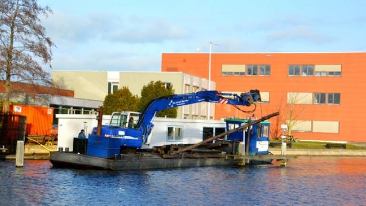 Een bouwbedrijf legt de woonboot aan de wal bij het kantoor van de FUMO, het voormalige gemeentekantoor.