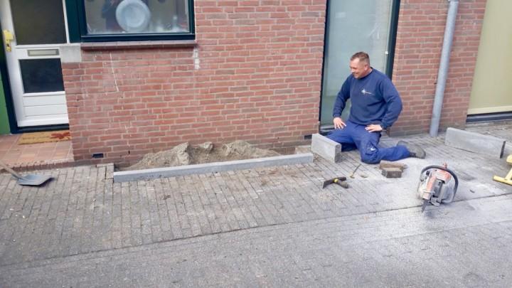 Een stratenmaker van de gemeente is bijna klaar met het eerste geveltuintje.