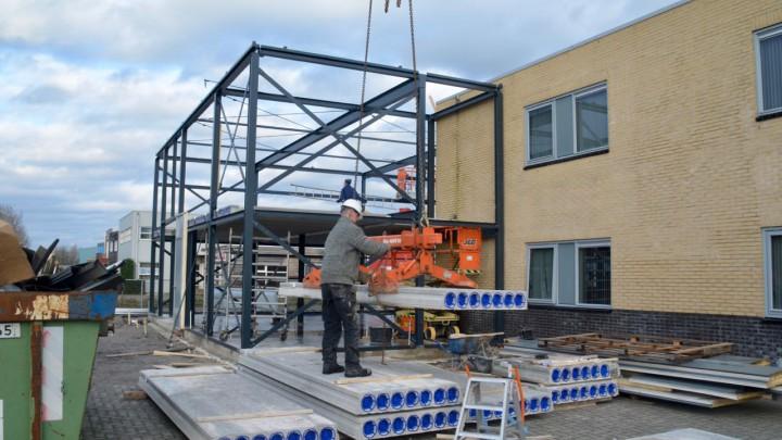 Een kraan van Kielstra takelt betonelementen naar de verdieping.