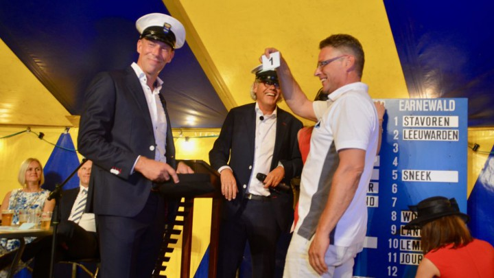 Johannes Meeter van het Huzumer Skûtsje trok nummer '1' uit de pet. Kommisjeleden Arno Huisma en Jan Feike Hoekstra kijken lachend toe.