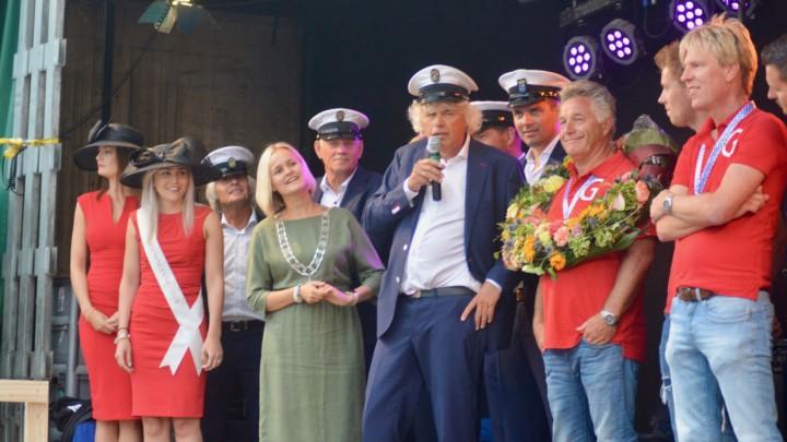 Jan Feike Hoekstra van de Skûtsjekommisje spreekt de honderden aanwezigen toe. Rechts schipper Douwe Visser in de kampioenskrans.