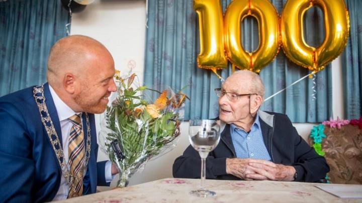 Loco-burgemeeter Hein de Haan (links) bracht de 100-jarige IJde Jonker een bloemetje.