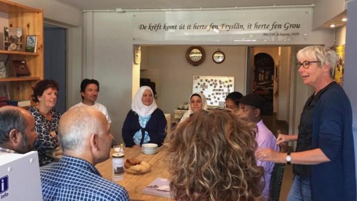 Enkele deelnemers aan de koffie en thee met Friese sûkerlatte tijdens de introductie door rondleider Gieneke Verhoeven (rechts). (Foto: Trinet Mulder)