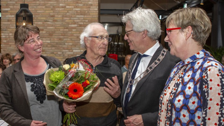 Burgemeester Crone feliciteert Jappie Holtrop met zijn jubileum. Jappie's dochters kijken verheugd toe.