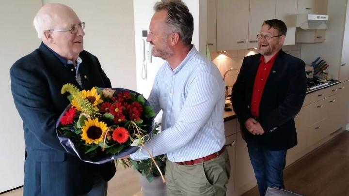Jelle van der Bijl kreeg het speldje en bloemen van zoon Hendrik-Dirk. Arie van Barneveld kijkt lachend toe. (Foto: Alinda Talsma)