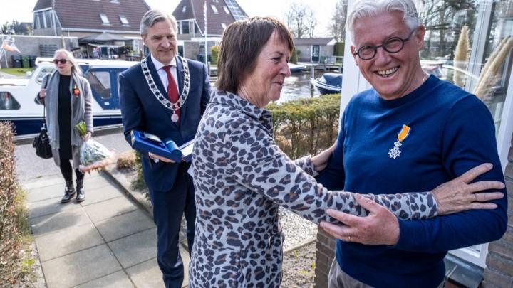 Burgemeester Buma heeft Jan Bijlsma onderscheiden. Zijn vrouw speldde hem de versierselen op. (Foto: Mark Grupstra)