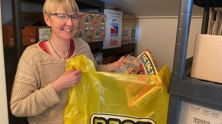Lenie Braks laat zien hoeveel gebruikte spullen er in de gele BEST-Tas kunnen.