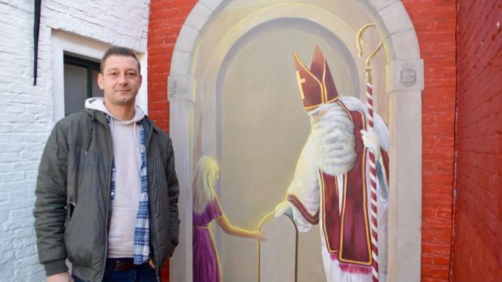 Kunstenaar L.J. van Tuinen poseert bij zijn fraaie muurschildering.