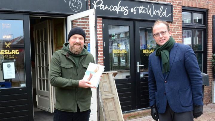 Johan Goslings, eigenaar van restaurant Beslag, ontving een exemplaar van 'Veelzijdig Grou' van wethouder Friso Douwstra. (Foto: Jikkie Piersma)