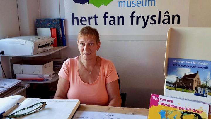 Gastvrouw Trees Mulder achter de balie van het museum.