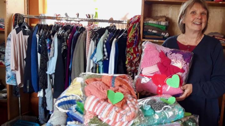 Annie Nicolai van Kinderkledingbank Grou temidden van de 12 babypakketten.