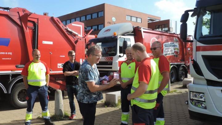 Coördinator oud papier Gabe Hoekstra overhandigt een afscheidspresentje aan Omrin-chauffeur Douwe.