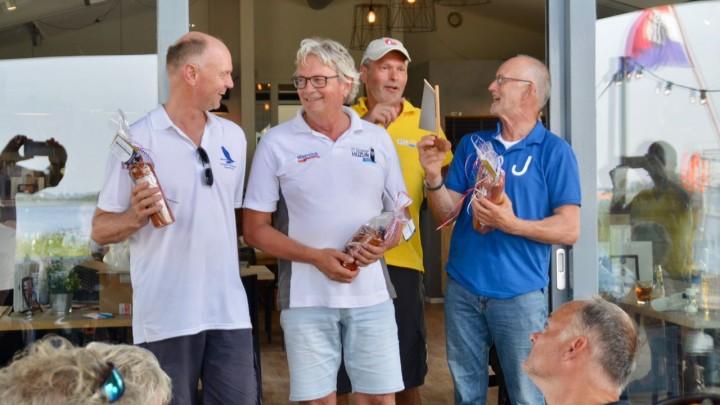 Durk Talsma van KWV Frisia  (in geel shirt) deelt de wisselprijs uit aan een bestuurslid van het Jouster skûtsje.