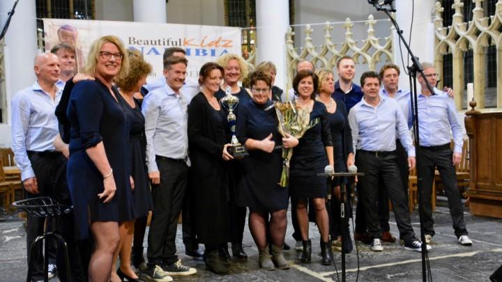Winnaar Sjonge Jonge met de beker. Er waren bloemen voor dirigent Akke Bosma.