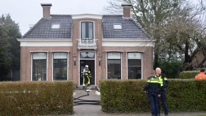 Een brandweerman gaat met perslucht de woning binnen. Aan de linkerzijde van de woning is nog wat rookontwikkeling te zien.
