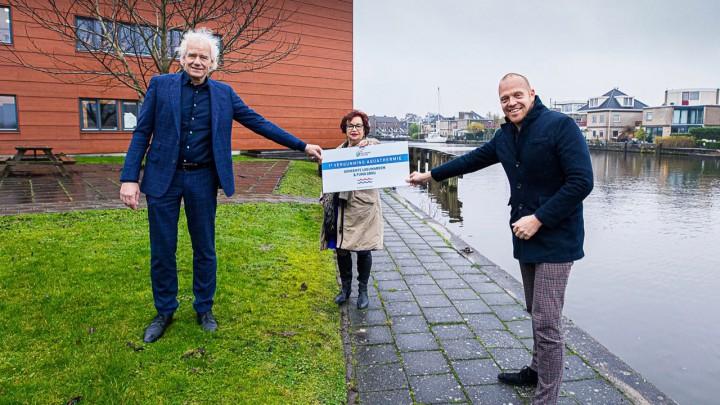 Annet van der Hoek, lid dagelijks bestuur Wetterskip Fryslân, overhandigt de aquathermie-vergunning aan wethouder Hein de Haan (rechts) van de gemeente Leeuwarden en directeur Pieter Hofstra (links) van de FUMO. (Foto: Daniël Hartog).
