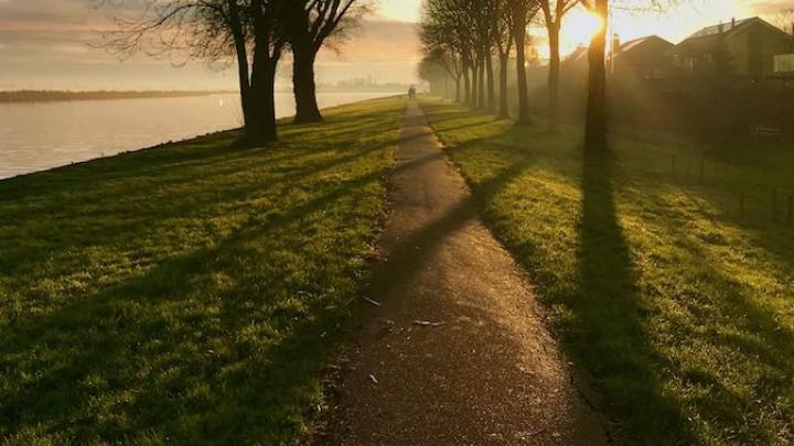 De zon gaat bijna onder boven het voetpad langs het kanaal. (Foto: Jannes Postma)